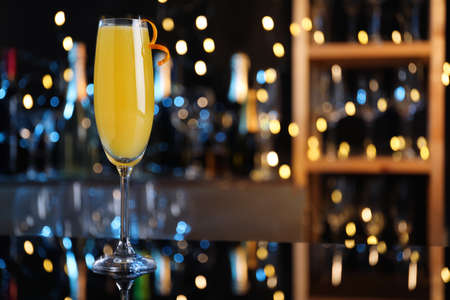 Mimosa cocktail with garnish on bar counter against blurred lights, space for text