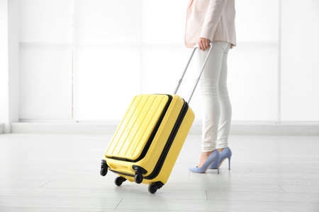 Businesswoman with yellow travel suitcase in airport