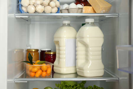Gallons of milk and different products in refrigerator, closeup