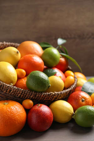 Different ripe citrus fruits on wooden table Stock Photo