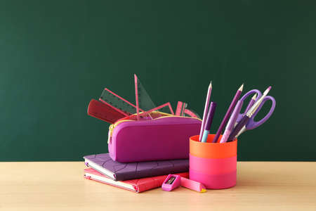 Different school stationery on wooden table near green chalkboard. Back to school