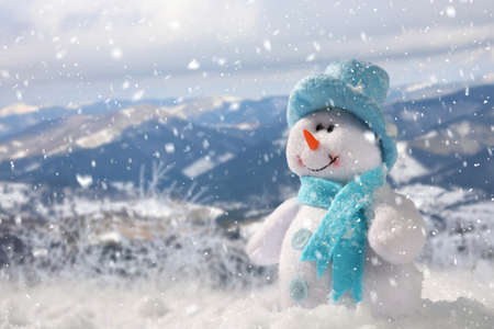Cute small decorative snowman outdoors on sunny day, space for text