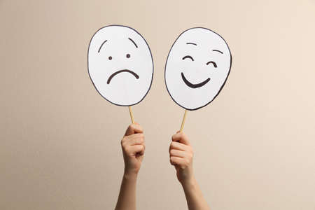Woman with sad and happy paper faces on beige background, closeup