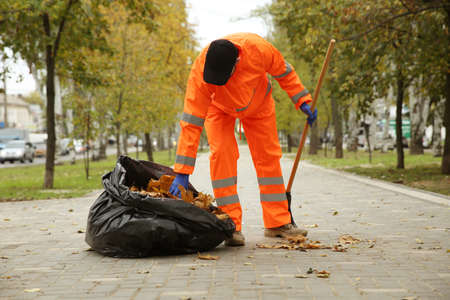 Worker cleaning street from fallen leaves on autumn day