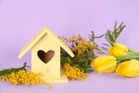Stylish bird house and fresh flowers on violet background