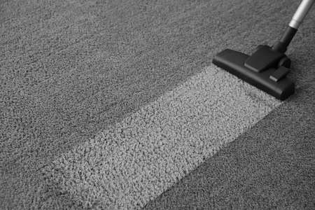 Modern vacuum cleaner on carpet. Space for text