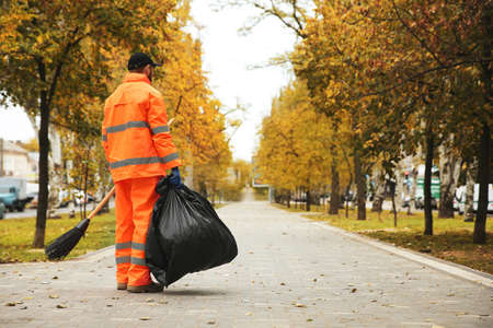 Street cleaner with broom and garbage bag outdoors on autumn day, back view