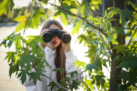 Jealous woman with binoculars spying on ex boyfriend outdoors