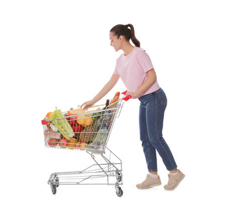 Happy woman with shopping cart full of groceries on white background