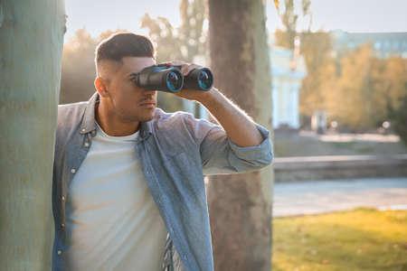 Jealous man with binoculars spying on ex girlfriend in park