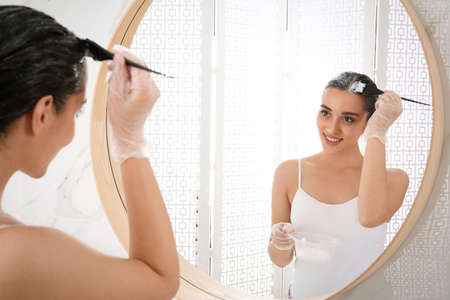 Young woman applying dye on hairs near mirror indoors