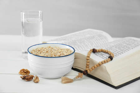 Oatmeal, rosary beads, Bible and glass of water on white table. Lent season