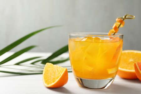 Delicious orange soda water on white table