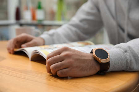 Man wearing smart watch and reading magazine at table indoors, closeup Archivio Fotografico