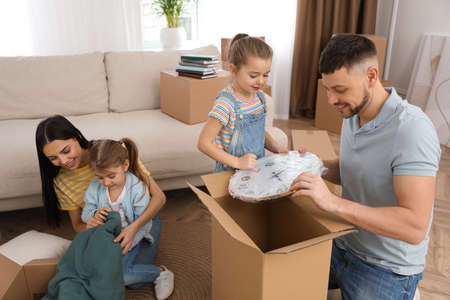 Happy family unpacking moving boxes at their new house
