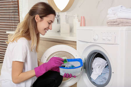 Woman holding container with laundry detergent capsules near washing machine indoors Banco de Imagens