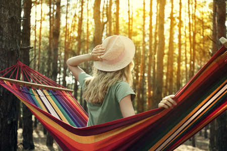 Woman resting in hammock outdoors on summer day