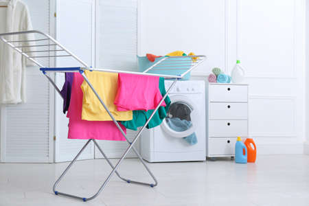 Clean bright laundry hanging on drying rack indoors