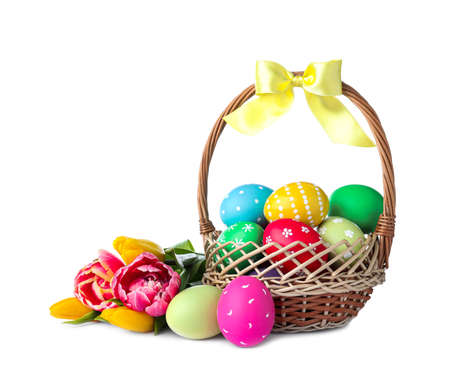 Wicker basket with bright painted Easter eggs and spring flowers on white background Zdjęcie Seryjne