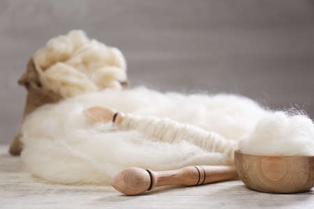 Soft white wool and spindles on wooden table. Space for text Standard-Bild