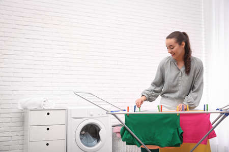 Young woman hanging clean laundry on drying rack indoors