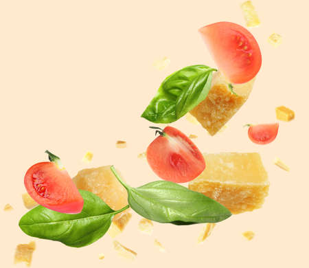Pieces of delicious parmesan, tomatoes and basil leaves falling on beige background
