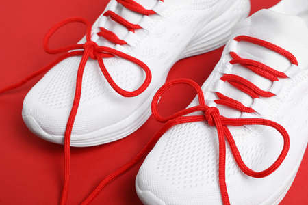 Stylish sneakers with shoe laces on red background, closeup