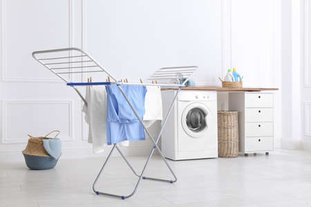 Clean laundry hanging on drying rack indoors