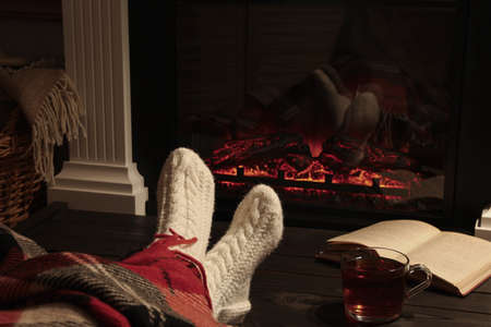 Woman with cup of tea and book resting near fireplace at home, closeup