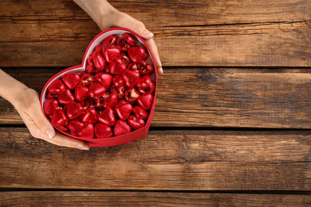 Woman holding box with heart shaped chocolate candies at wooden table, top view. Space for text Stock Photo