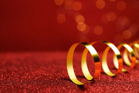Shiny golden serpentine streamer on red table against blurred lights, closeup. Space for text