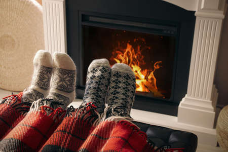 Couple resting near fireplace at home, closeup