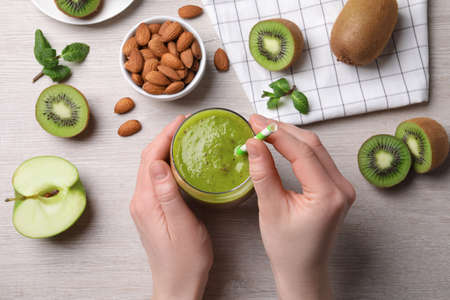 Woman with delicious kiwi smoothie and ingredients at white wooden table, top view