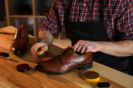 Craftsman taking professional care of brown leather shoes in workshop, closeup Stock Photo