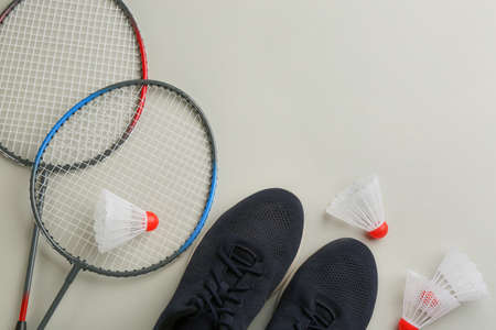 Badminton rackets, shuttlecocks and shoes on light grey background, flat lay. Space for text