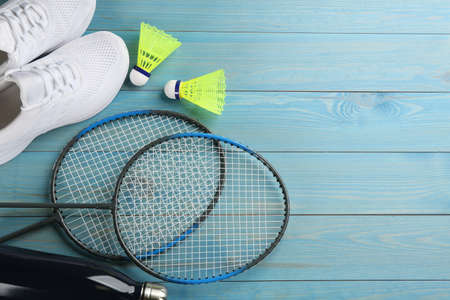 Rackets, shoes and shuttlecocks on light blue wooden table, space for text. Playing badminton