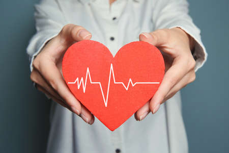 Woman holding red heart with cardiogram, closeup