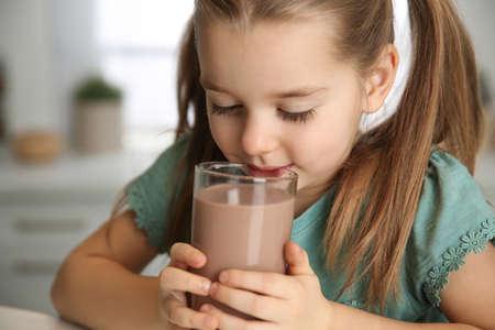 Cute little child drinking tasty chocolate milk in kitchen, closeup Foto de archivo