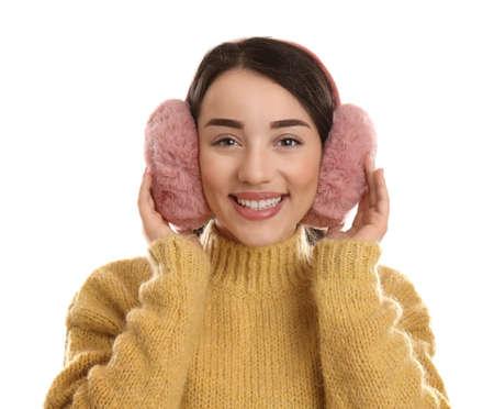 Beautiful young woman wearing earmuffs on white background Reklamní fotografie