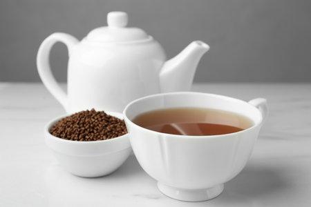 Delicious buckwheat tea and granules on white table Banco de Imagens