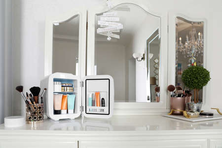 Mini fridge with cosmetic products on white vanity table