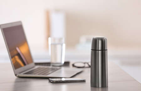 Thermo bottle on table in modern office