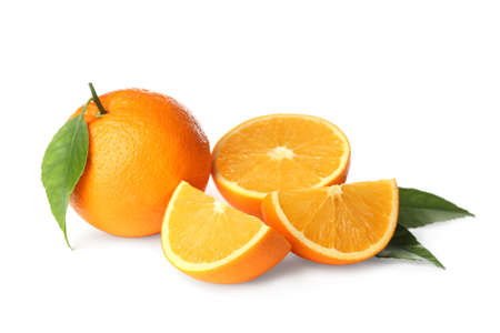 Cut and whole fresh ripe oranges with green leaves on white background