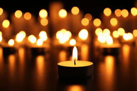 Burning candle on black table. Memory day