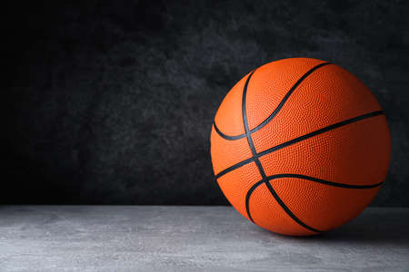 Orange ball on light grey table, space for text. Basketball equipment