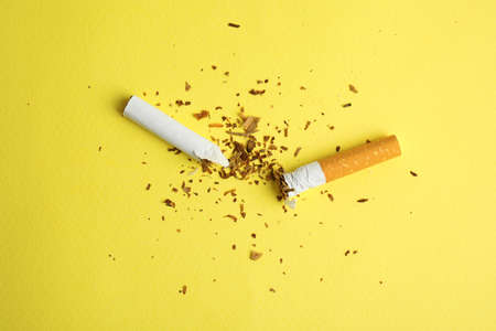 Broken cigarette on yellow background, flat lay. Quitting smoking concept Stock Photo