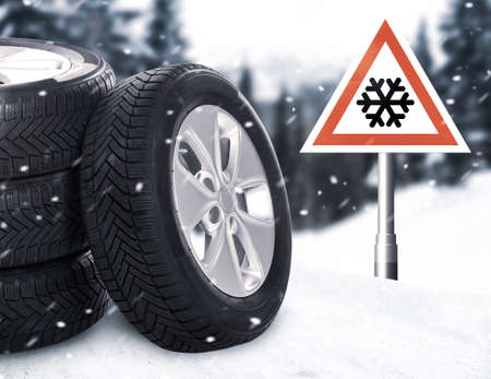 Set of wheels with winter tires on snow and road sign outdoors