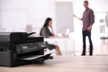 New modern printer on table in office. Space for text
