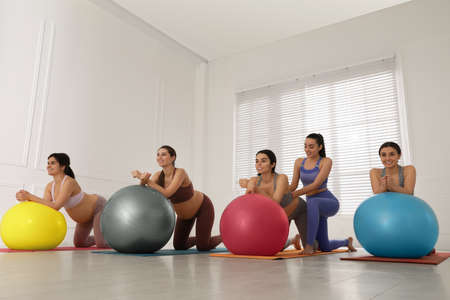 Trainer working with group of pregnant women in gym. Preparation for child birth