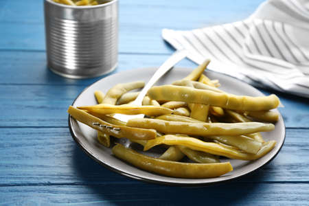 Canned green beans on blue wooden table, closeup